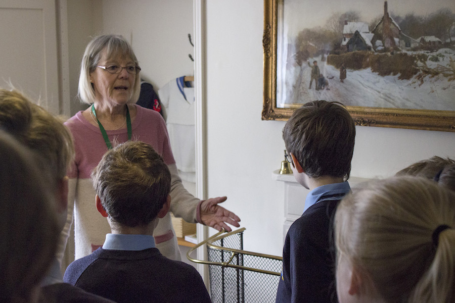 A volunteer guides a school party around the Holst Birthplace Museum